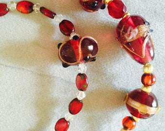 Lamp work cranberry red and gold murano glass necklace. bracelet, earrings.