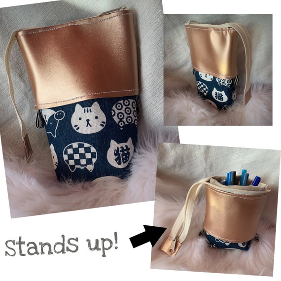 So clever! Sliding stand up pencil pouch in a sweet indigo Japanese cat print accented with lustrous rose gold faux leather.