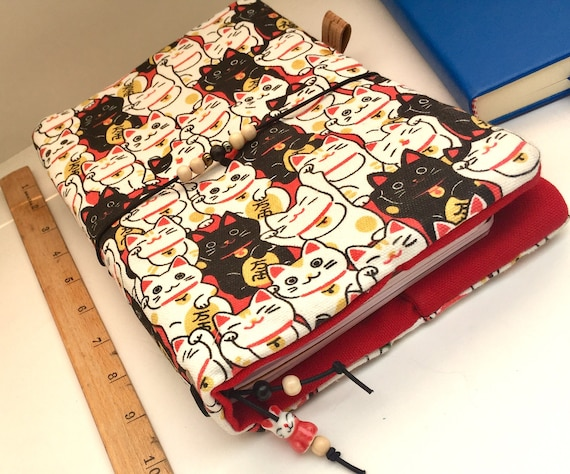 Lucky cat refillable notebook in A5 size! The bold printed canvas and copious handmade charm of this notebook will turn heads