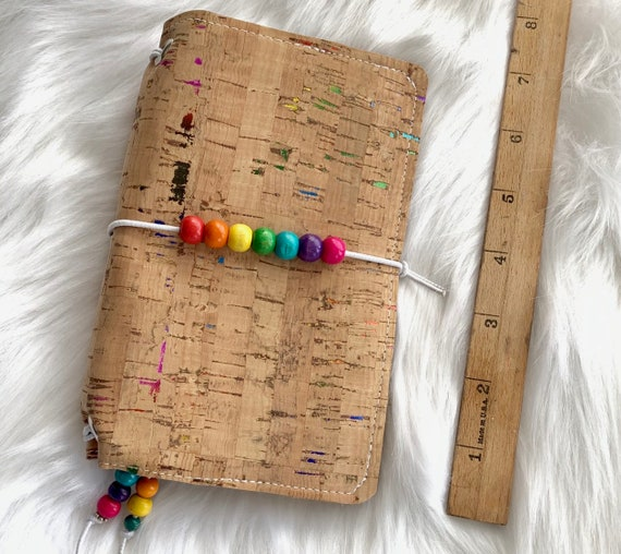 Field notes size TN natural cork traveler's notebook with rainbow foil flecks and colorful wooden beads. Artist made notebook includes inse