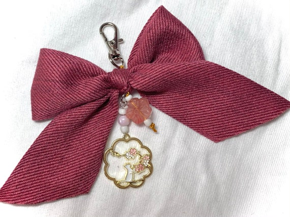 Opulent bow charm with soft cotton ribbon, enamel cat pendant, and natural carved stone blossom bead to embellish your planner or bag!