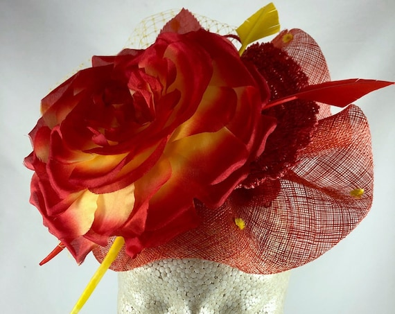 Coral-red and yellow silk rose on coral-red straw fascinator with yellow dot veiling and feather arrows