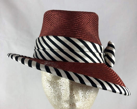 Rust parasisal straw fedora with black Bakelite buckle and black and white striped silk band and binding