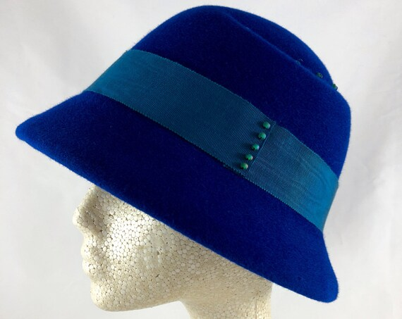 Royal blue velour felt cloche with indented asymmetrical crown, turquoise petersham band and glass beading details