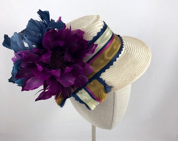Off-white parasisal straw percher with antique striped silk ribbon band and purple and navy feather flowers on navy headband