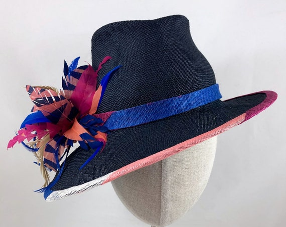 Navy parasisal straw fedora with asymmetrical brim, striped band and binding, and colorful feather spray