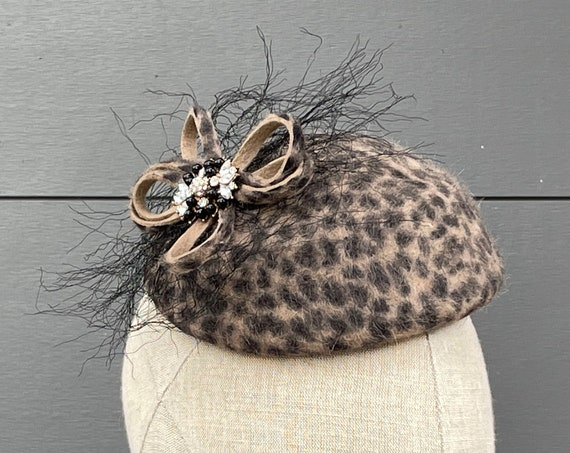Leopard print button pillbox hat percher with rhinestone, felt loop, and fringe ornament