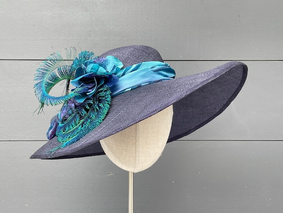 Wide-brimmed navy straw hat with handmade silk flowers and curled peacock sword feathers