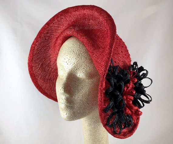 Red knotted hand-draped straw cloche with black and red straw braid hatband and flowers