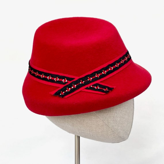 Red velour felt perching hat with layered trim of red petersham ribbon and antique black and metal ribbon