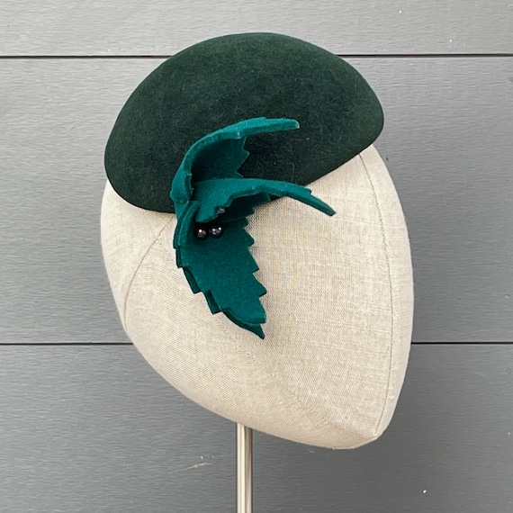 Forest green velour felt perching hat with teal green felt leaves and black pearls