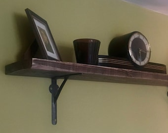 Industrial style reclaimed wood shelf mounted on iron gallows brackets