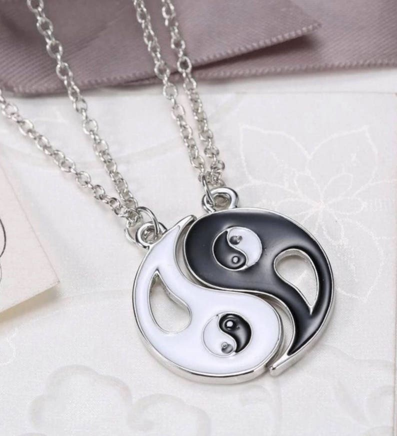 A Pair of Ying and Yang Necklaces on 18 Inch Chains.