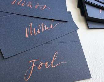 Wedding place cards made from premium navy blue card stock with hand lettered copper or gold ink calligraphy of first name.
