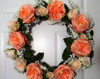 Peach cabbage roses surrounded by pink baby roses