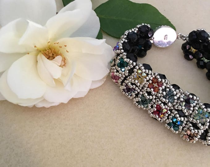 Swarovski Crystal bracelet on black base. Multi colored 3mm bicones adorned the 1 inch wide bracelet