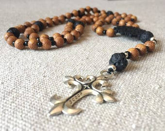 Lava stone and wood beaded necklace in a Seven Season rosary style, with a silver tone cross.