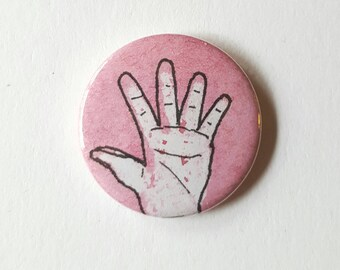 Red hand pin badge