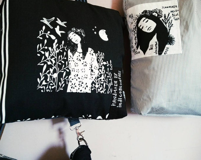 Zippered , lined, big,cross body, internal pockets, black tote bag, with white prints.