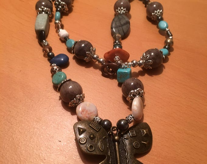 Handmade beaded necklace made of multicolored beads with a predominance of blue and a butterfly pendant