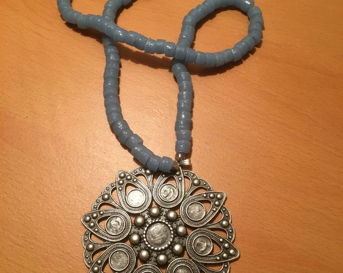A sky-blue colored bead necklace with a silver colored pendant