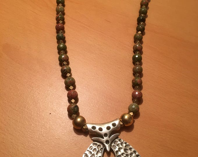 Handmade beaded necklace made of green and red speckled beads with a silver colored elephant face pendant