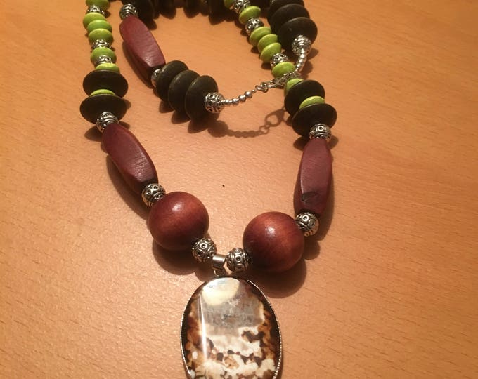 Handmade beaded necklace made of light green wooden beads, large brown wooden beads and a brown pendant
