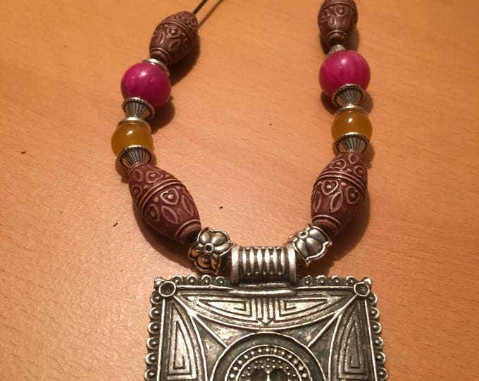 Handmade beaded necklace, A square silver colored pendant on a black leather chord with pink and yellow beads.