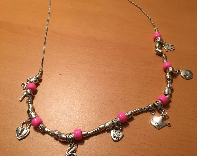Handmade beaded necklace made of metal beads, pink beads, charms and silver colored chain