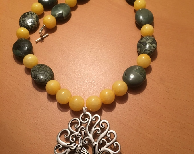 Handmade beaded necklace made of large yellow and large greenish gray colored beads with a pendant.