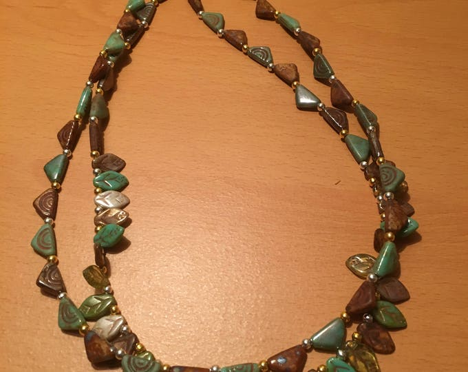 Handmade double stranded bead necklace made of small green leaves and triangles.