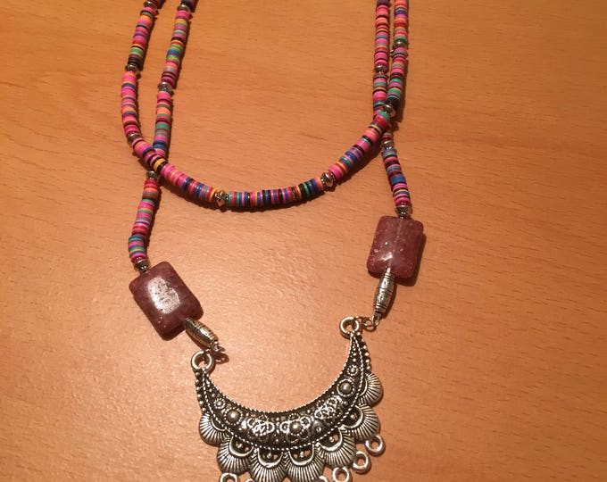 Handmade beaded necklace made of pink waist beads and crescent shaped silver colored pendant