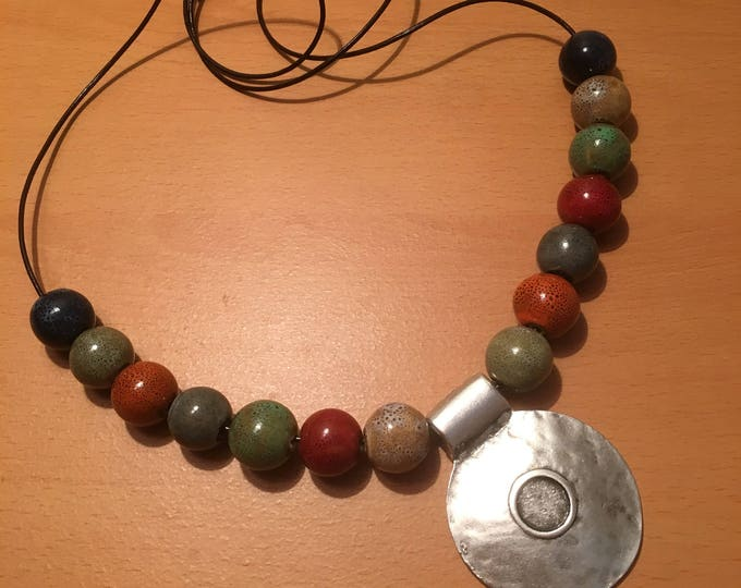 A handmade multicolored beaded necklace with a silver colored pendant on a leather chord