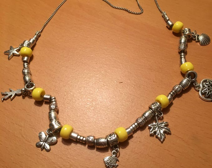 Handmade metal beaded necklace with yellow beads and metal charms