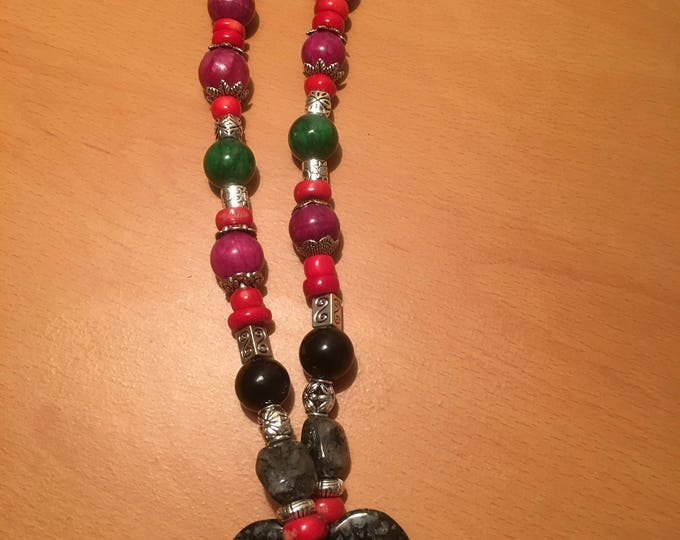 Handmade beaded necklace made of pink red and green colored beads with a black heart shaped pendant