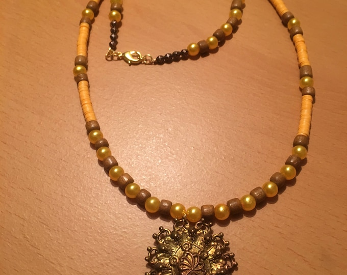 Handmade beaded necklace made of small yellow beads, african waist beads and wooden beads with a metal pendant