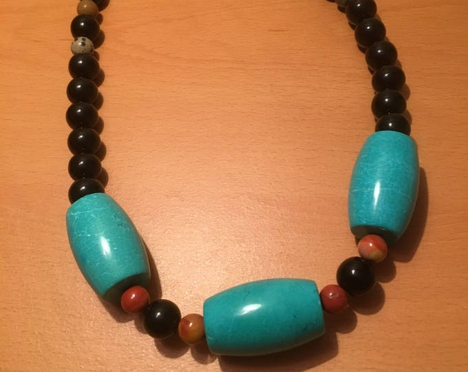 Handmade beaded necklace made of large blue exotic beads, multicolored and black beads