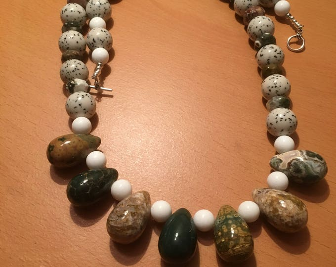 Handmade beaded necklace made of white, black and white speckled and large brown and greenish colored beads