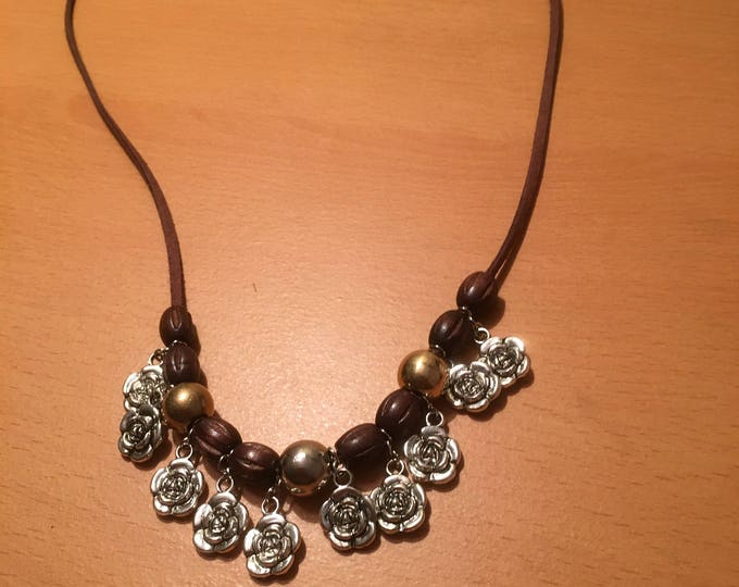 Handmade beaded necklace with brown wooden beads, metal beads and rose charms on a brown faux leather chord