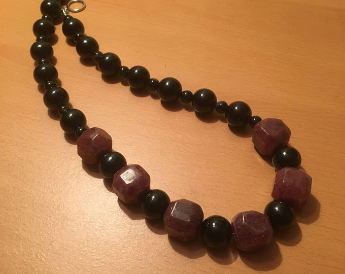 Handmade beaded necklace made of large pink beads and black beads