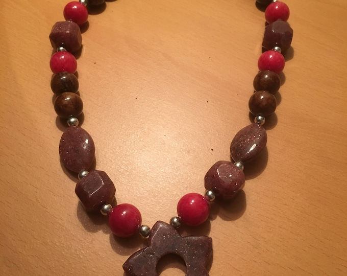 Handmade beaded necklace made of red and pink dyed jade beads with silver colored rondelles