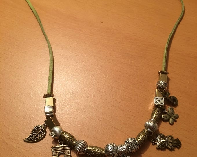 Handmade beaded necklace made of metals beads and charms on a green faux leather chord