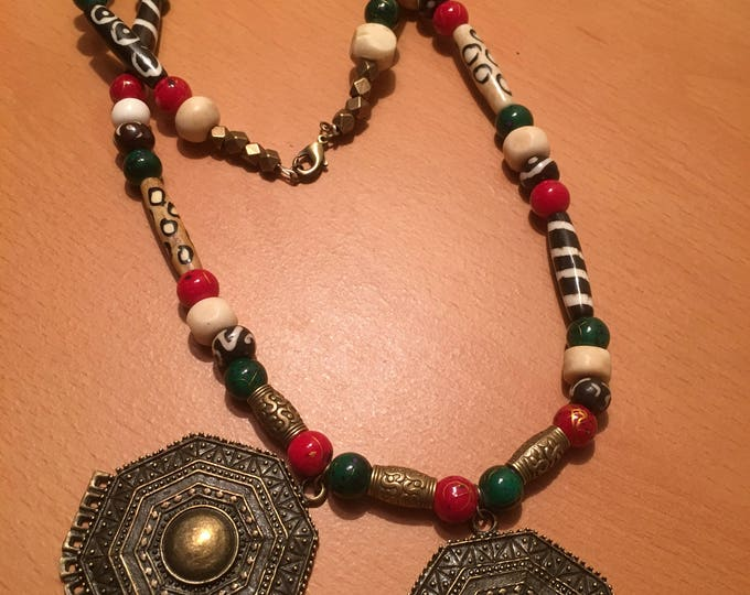 Handmade beaded necklace. A double brass colored pendant necklace with red green and beige beads