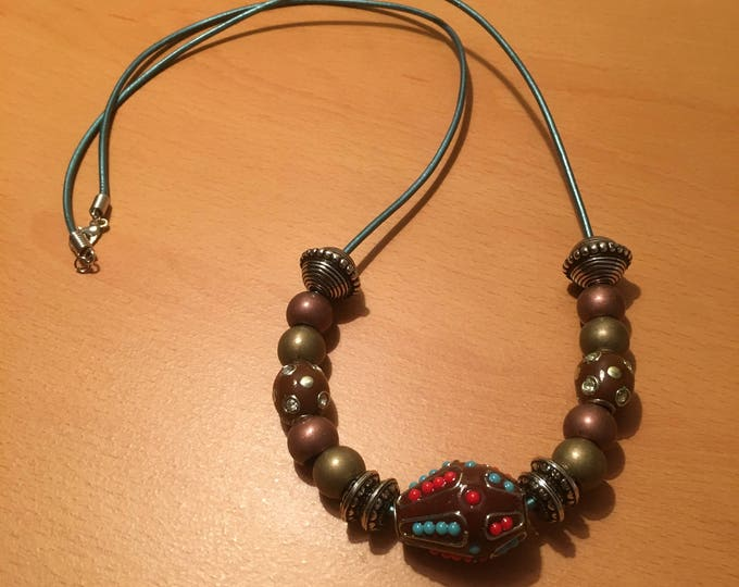 A beaded necklace made of large metal and exotic beads