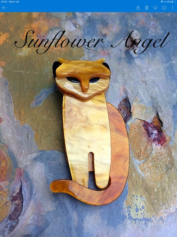 Art Deco 3D cat brooch. In golden shimmer, with black eyes and ears.