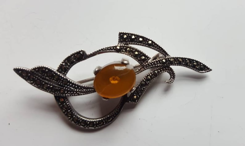 Lovely curvy design Pretty Art Deco silver brooch with centre Amber cabachon and marcasite Very stylish and wearable.