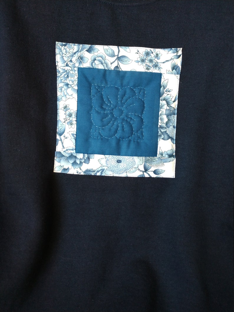 Navy sweatshirt with hand quiilted flower block surrounded by delft blue floral border