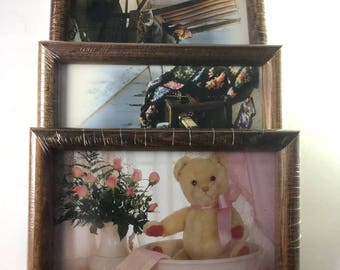 "Three 6""x 8"" picture frames, New in plastic, medium brown wood grain"