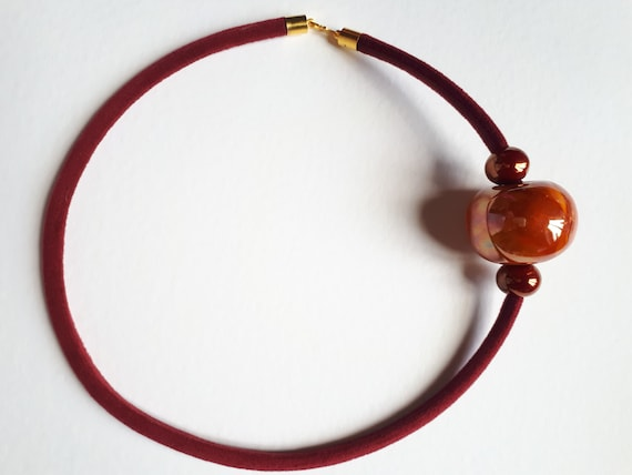 Crew neck necklace with burnt orange ceramic panel