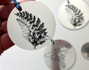 The Last of Us Christmas tree ornament, metallic silver. Fireflies symbol and Ellie's tattoo from TLOU2, laser engraved. TLOU